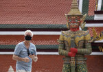 A visitor wearing a face mask to help curb the spread of the coronavirus tours the Temple of the Emerald Buddha in Bangkok, Thailand, Monday, June 8, 2020. Thai authorities have allowed the temple, a popular tourist site, and other businesses to reopen as they selectively ease restrictions protecting against the coronavirus. (AP Photo/Sakchai Lalit)