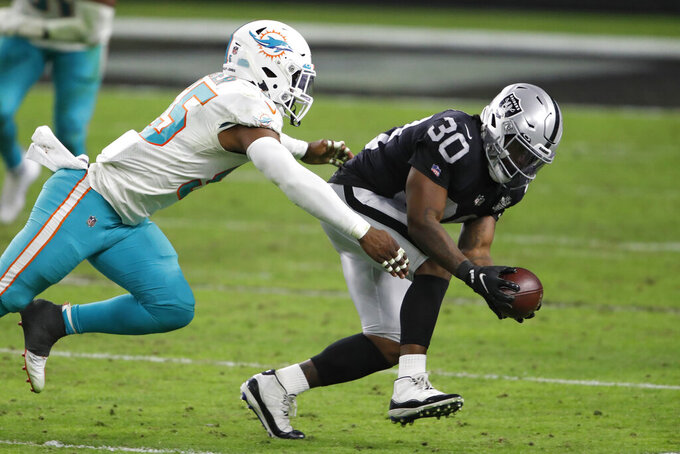Las Vegas Raiders running back Jalen Richard (30) catches a pass against Miami Dolphins outside linebacker Jerome Baker (55) during the second half of an NFL football game, Saturday, Dec. 26, 2020, in Las Vegas. (AP Photo/Steve Marcus)
