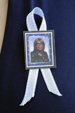 A ribbon for Tennessee Department of Correction administrator Debra Johnson is worn by a visitor attending her funeral Friday, Aug. 16, 2019, in Nashville, Tenn. Officials say inmate Curtis Watson killed Johnson before his escape from the West Tennessee State Penitentiary Aug. 7. (AP Photo/Mark Humphrey)
