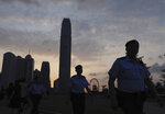 Police officers patrol a park as the sunset near the Legislative Council in Hong Kong on Saturday, June 15, 2019. Hong Kong's Chief Executive Carrie Lam said she will suspend a proposed extradition bill indefinitely in response to widespread public unhappiness over the measure, which would enable authorities to send some suspects to stand trial in mainland courts. (AP Photo/Vincent Yu)