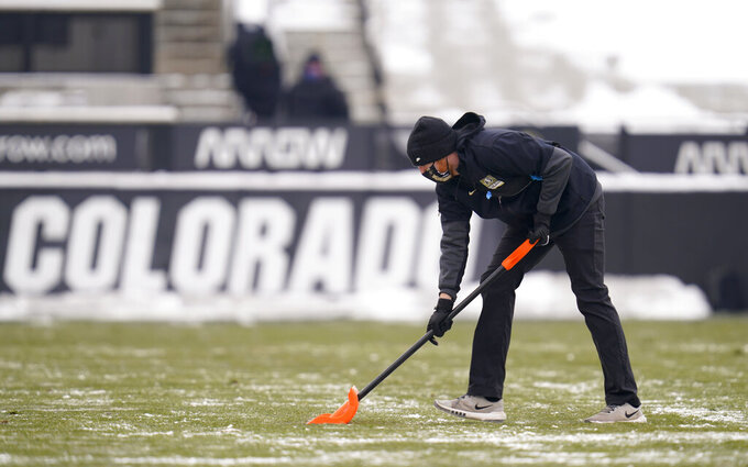 A field worker uses a shovel to clear the lines before the first half of an NCAA college football game as Colorado hosts Utah Saturday, Dec. 12, 2020, in Boulder, Colo. (AP Photo/David Zalubowski)