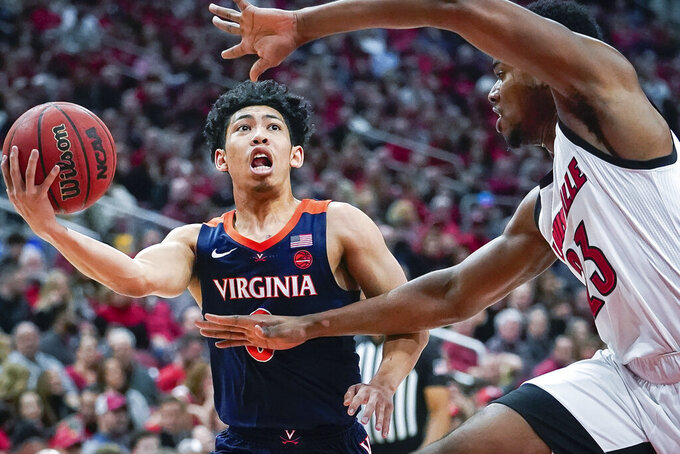Virginia guard Kihei Clark (0) drives toward the basket around Louisville center Steven Enoch (23)during the first half of an NCAA college basketball game, Saturday, Feb 8, 2020 in Louisville, Ky. (AP Photo/Bryan Woolston)