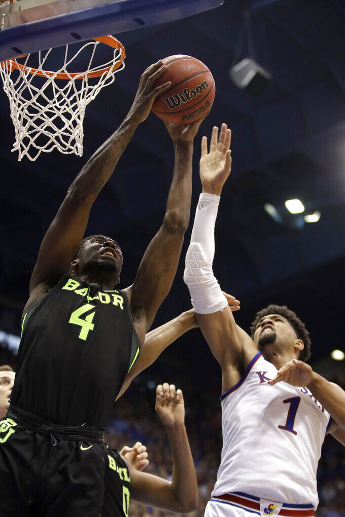 Baylor's Mario Kegler (4) beats Kansas' Dedric Lawson (1) to a rebound during the first half of an NCAA college basketball game Saturday, March 9, 2019, in Lawrence, Kan. (AP Photo/Charlie Riedel)