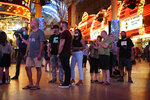 People wait in line to enter after the reopening of the D Las Vegas hotel and casino Thursday, June 4, 2020, in Las Vegas. Casinos were allowed to reopen early Thursday after temporary closures as a precaution against the coronavirus. (AP Photo/John Locher)