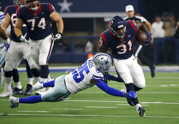 Dallas Cowboys free safety Xavier Woods (25) attempts to stop Houston Texans running back Karan Higdon (31) from advancing the ball in the first half of a preseason NFL football game in Arlington, Texas, Saturday, Aug. 24, 2019. (AP Photo/Michael Ainsworth)