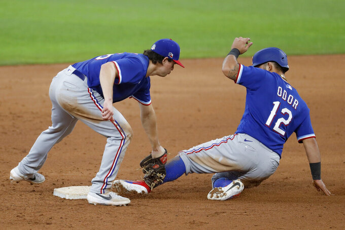Texas Rangers second baseman Nick Solak, left, tags out Rougned Odor on a stolen base-attempt during an intrasquad practice baseball game at Globe Life Field in Arlington, Texas, Monday, July 6, 2020. (AP Photo/Tony Gutierrez)