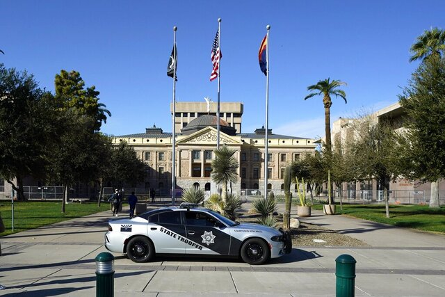 An Arizona State Trooper vehicle drives in front of the Arizona Capitol Wednesday, Jan. 20, 2021, in Phoenix. (AP Photo/Ross D. Franklin)