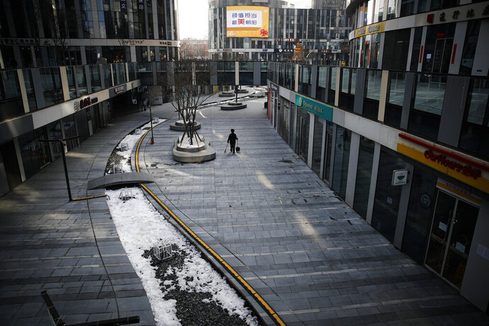 FILE - In this Feb. 10, 2020, file photo, a cleaner walks through a deserted compound of a commercial office building in Beijing. Chinese authorities are struggling to strike a delicate balance between containing a deadly viral outbreak and restarting the world's second-biggest economy after weeks of paralysis. (AP Photo/Andy Wong, File)