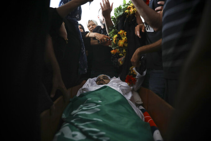 Palestinian mourners gather around the body of Mohammad Kiwan, 17, whose family says he was killed in clashes with Israeli police in the Arab town of Umm al-Fahm, Thursday, May 20, 2021. Police say the May 12 shooting is under investigation. (AP Photo/Mahmoud Illean)