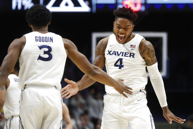 Xavier's Tyrique Jones (4) reacts with Quentin Goodin (3) during the first half of the team's NCAA college basketball game against Marquette, Wednesday, Jan. 29, 2020, in Cincinnati. (AP Photo/John Minchillo)