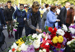 People lay flowers to commemorate the victims of the attack on a vocational college, in Kerch, Crimea, Thursday, Oct. 18, 2018. Authorities on the Crimean Peninsula were searching for a possible accomplice of the student who carried out a shooting and bomb attack on a vocational school Wednesday, killing 20 people and wounding more than 50 others, an official said Thursday. (AP Photo/Sergei Demidov)
