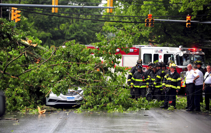 In this Wednesday, July 17, 2019 photo, emergency personnel work at the scene after a tree fell on a vehicle along Park Ave. in Bridgeport, Conn, Firefighters had to wait nearly an hour for an electrical crew to shut down power to the wires before they could remove 21-year-old Jarrod Marotto. A series of powerful thunderstorms was moving through the area at the time. (Christian Abraham/Hearst Connecticut Media via AP)
