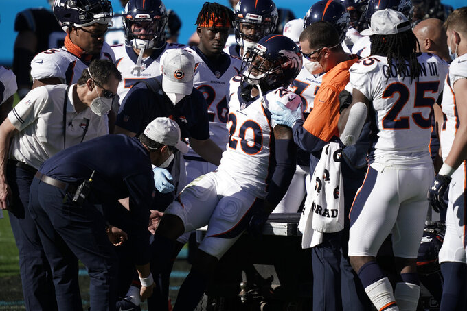 Denver Broncos cornerback Duke Dawson Jr. is helped off the field after getting hunt during the first half of an NFL football game against the Carolina Panthers Sunday, Dec. 13, 2020, in Charlotte, N.C. (AP Photo/Gerry Broome)