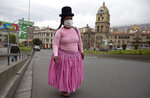 A woman walks in an empty street near the Basilica of San Francisco during a government ordered lockdown, which limits residents to shopping in the morning, as a measure to help contain the spread of the new coronavirus in La Paz, Bolivia, Tuesday, April 7, 2020. (AP Photo/Juan Karita)