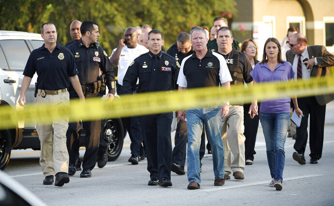 FILE - In this Sunday, June 12, 2016 file photo, Mayor Buddy Dyer, center right, and then-Police Chief John Mina, center left, arrive for a news conference after the mass shooting at the Pulse Orlando nightclub in Orlando, Fla. Mina, now the Orange County, Fla., sheriff, says after the attack, police officers were equipped with another layer of body armor that stops rifle rounds. (AP Photo/Phelan M. Ebenhack)