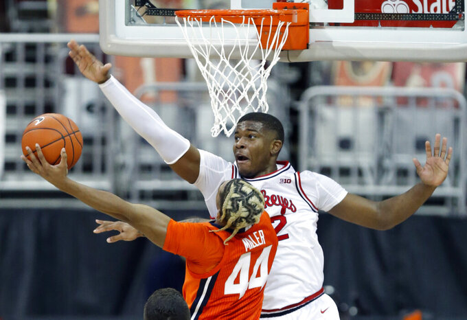 FILE - Ohio State forward E.J. Liddell, top, tries to block a shot by Illinois guard Adam Miller during the second half of an NCAA college basketball game in Columbus, Ohio, in this Saturday, March 6, 2021, file photo. Liddell was named to The AP All-Big Ten first team, announced Tuesday, March 9, 2021. (AP Photo/Paul Vernon, File)