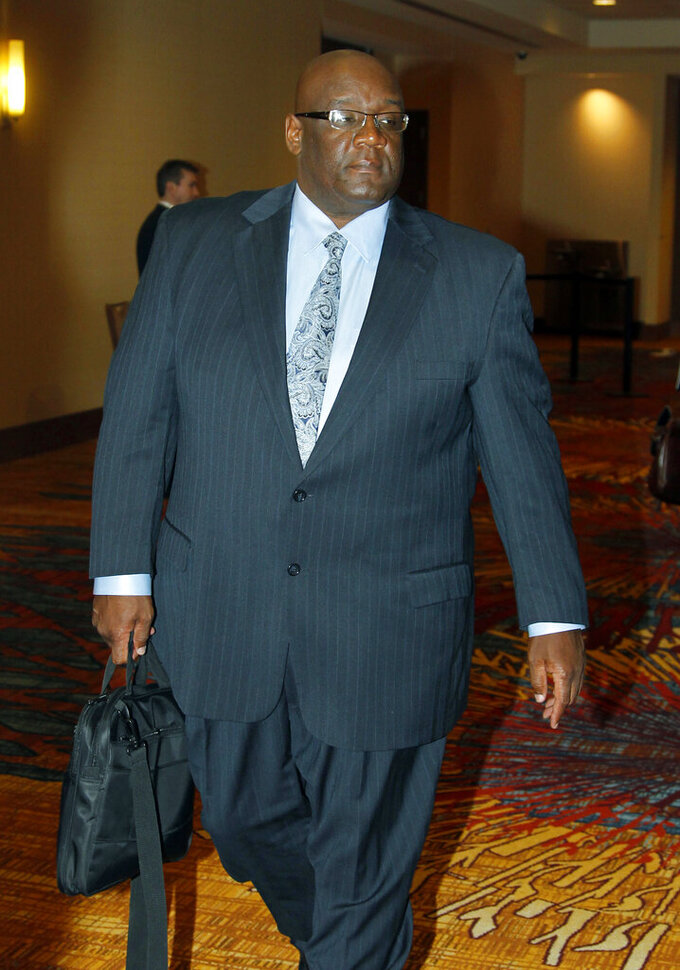 FILE - In this Oct. 28, 2011 file photo, former University of North Carolina associate head football coach coach John Blake leaves during a break at an NCAA infractions committee hearing in Indianapolis. Blake, a former Oklahoma football player and Oklahoma's first Black head coach in any sport, has passed away. He was 59. (AP Photo/Michael Conroy, file)