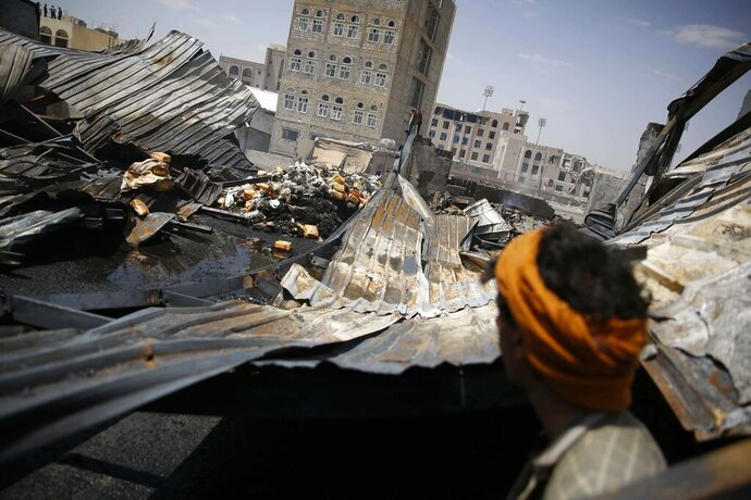 FILE - In this Thursday, Sept. 17, 2015, file photo, a worker looks at a chocolate factory destroyed by a Saudi-led airstrike in Sanaa, Yemen. Envoys from Yemen's warring parties are headed to Sweden for another round of peace talks to stop the three-year-old war, but with few incentives to compromise, expectations are low for little more than improving a faltering de-escalation.(AP Photo/Hani Mohammed, File)