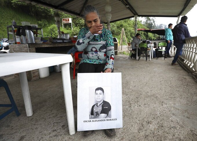 """Doris Tejada, mother of Oscar Alexander Morales who disappeared on New Year's eve 2007, holds a photo of her son, at a shop in Soacha, Colombia, Thursday, April 8, 2021. Tejada and her husband found out that their son indeed is on the list of the """"false positives,"""" victims of extrajudicial executions by members of Colombia's army who were falsely presented as guerrillas killed in combat during the country's internal conflict, which ended with the 2016 demobilization of the Revolutionary Armed Forces of Colombia. (AP Photo/Fernando Vergara)"""