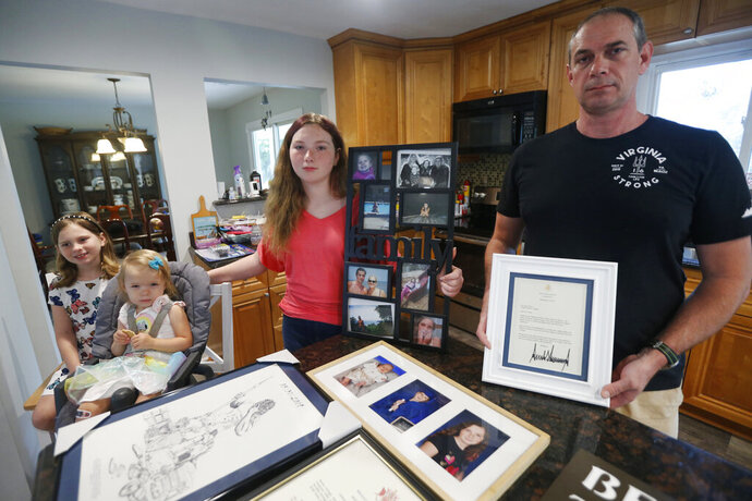 In this May 22, 2020, photo, Jason Nixon, right, holds a letter from President Donald Trump as he poses with his children, Mackenzie, left, Madilyn, second from left and Morgan as they display memorabilia from last years shooting that took the life of Kate Nixon at their home in Virginia Beach, Va. As the shooting's one-year anniversary approaches this weekend, some of the victim's family members say the rampage is effectively forgotten. (AP Photo/Steve Helber)