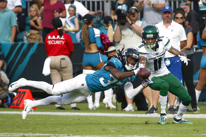 Jacksonville Jaguars cornerback Tre Herndon, left, intercepts a pass intended for New York Jets wide receiver Robby Anderson (11) during the second half of an NFL football game, Sunday, Oct. 27, 2019, in Jacksonville, Fla. (AP Photo/Stephen B. Morton)