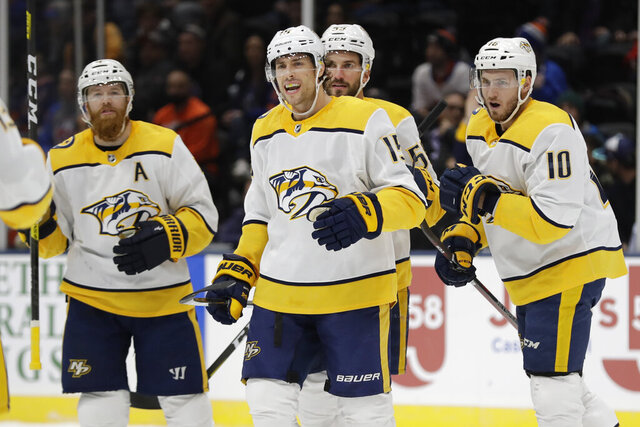 Nashville Predators' Craig Smith (15) celebrates with teammates Ryan Ellis, left, and Colton Sissons, right, after scoring a goal during the first period of an NHL hockey game against the New York Islanders, Tuesday, Dec. 17, 2019, in Uniondale, N.Y. (AP Photo/Frank Franklin II)