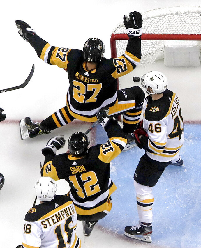 Pittsburgh Penguins' Nick Bjugstad (27) celebrates his goal in the first period of an NHL hockey game with Boston Bruins' David Krejci (46) defending in Pittsburgh, Sunday, March 10, 2019. The Penguins won 4-2. (AP Photo/Gene J. Puskar)