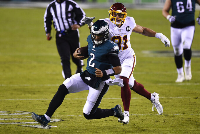 Philadelphia Eagles' Jalen Hurts (2) tries to get past Washington Football Team's Ryan Kerrigan (91) during the first half of an NFL football game against the Washington Football Team, Sunday, Jan. 3, 2021, in Philadelphia. (AP Photo/Derik Hamilton)