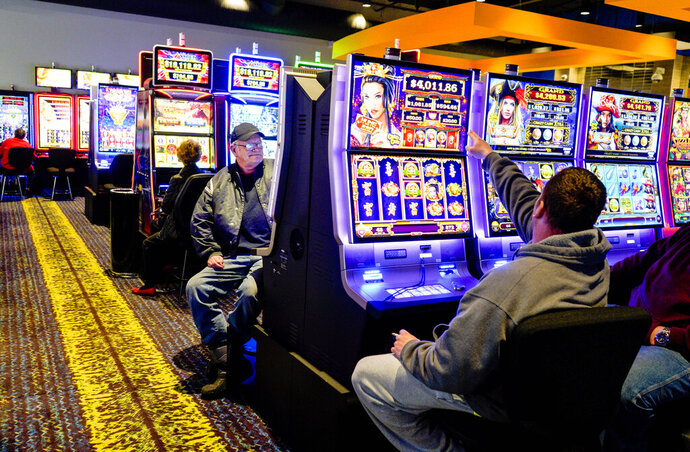 FILE - In this Feb. 14, 2019, file photo, patrons plays the slots at the Ponca Tribe's Prairie Flower Casino in Carter Lake, Iowa. On Monday, Aug. 12, 2019, the Ponca Tribe of Nebraska has again scored a legal win in its fight to keep its Prairie Flower Casino in western Iowa open after a federal judge rejected motions by the states of Iowa and Nebraska and the Iowa city of Council Bluffs seeking to derail the casino. (AP Photo/Nati Harnik, File)