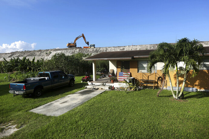 In this Friday, Nov. 1, 2019 photo, rehabilitation work takes place on top of the Herbert Hoover Dike surrounding Lake Okeechobee, just a few feet from a home in Pahokee, Fla. Hurricane tides overtopped the original dike in 1926 and 1928, washed away houses and caused over 2,500 deaths. (AP Photo/Robert F. Bukaty)