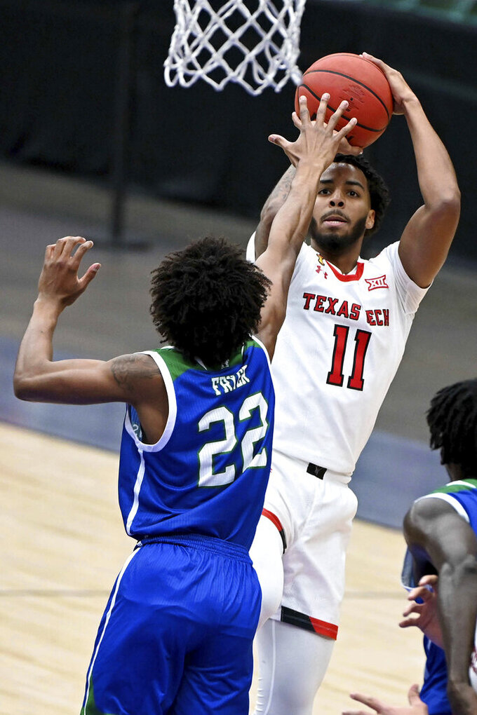 Texas Tech guard Kyler Edwards (11) shoots over Texas A&M-CC guard Simeon Fryer (22) in the first half of an NCAA college basketball game in Frisco, Texas, Saturday, Dec. 12, 2020. (AP Photo/Matt Strasen)