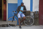 A man surfs the internet on his smartphone in Havana, Cuba, Thursday, Dec. 6, 2018. For the first time, Cubans are able to sign up for 3G internet service for their mobile phones, with packages ranging from 600 megabytes for about $7 to four gigabytes for about $30 month. (AP Photo/Desmond Boylan)