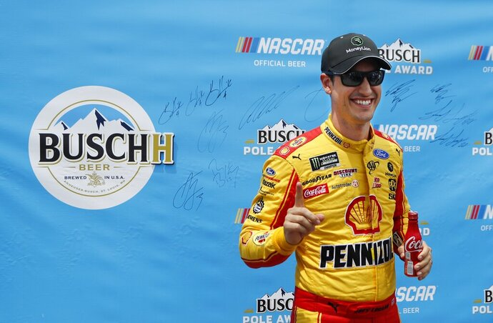 Joey Logano signals No. 1 during the pole award presentation after qualifying for the NASCAR cup series race at Michigan International Speedway, Saturday, June 8, 2019, in Brooklyn, Mich. (AP Photo/Carlos Osorio)