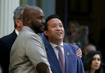 FILE - In this Sept, 11, 2019 file photo Assemblyman David Chiu, D-San Francisco, right, accompanied by Assemblyman Mike Gipson, D-Carson, left, smiles as his measure to cap rent increases is approved by the Assembly in Sacramento, Calif. Chiu's bill was one of the priorities of Democrats in this year's legislative session that ended Friday, Sept. 13. (AP Photo/Rich Pedroncelli, File)