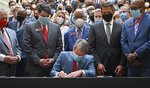 Gov. Brian Kemp, center, signs HB 426, hate-crimes legislation, into law on the last day of the legislative session at Georgia State Capitol, Friday, June 26, 2020. Kemp signed into law House Bill 426 which would impose additional penalties for crimes motivated by the victim's race, color, religion, national origin, sexual orientation, gender or disability. (Hyosub Shin/Atlanta Journal-Constitution via AP)
