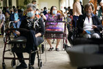 FILE - In this Tuesday, Jan. 12, 2021 photo, Resident Sabeth Ramirez, 80, center, waits in line with others for the Pfizer-BioNTech COVID-19 vaccine at the The Palace assisted living facility in Coral Gables, Fla. Florida Gov. Ron DeSantis is walking back his claims Friday, Jan. 22, that his state has now vaccinated 1 million seniors. State officials acknowledged that it could take a few more days to reach the milestone. (AP Photo/Lynne Sladky, File)