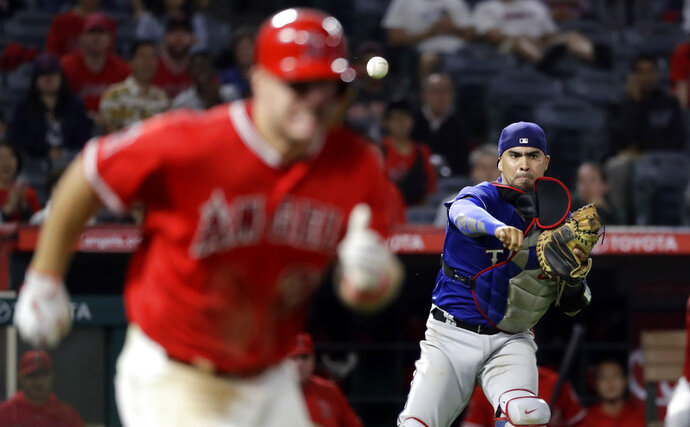 FILE - In this Sept. 10, 2018, file photo, Texas Rangers catcher Robinson Chirinos, right, throws out Los Angeles Angels' Mike Trout, left, at first base after a ground ball during the ninth inning of a baseball game in Anaheim, Calif. Chirinos and the Houston Astros have finalized a $5.75 million, one-year contract, giving catching-thin Houston another option behind the plate. (AP Photo/Marcio Jose Sanchez, File)