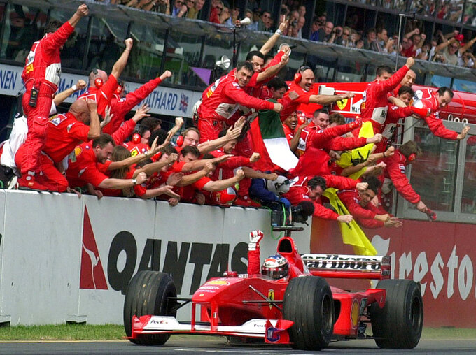 FILE - In this March 12, 2000, file photo, Ferrari's F1 driver Michael Schumacher, of Germany, is cheered by his pit crew as he heads for the finish line to win the Australian Grand Prix auto race in Melbourne, Australia. Schumacher's family, in a statement Wednesday, Jan. 2, 2019, has asked for understanding as it continues to keep details of his health private ahead of the seven-time Formula One champion's 50th birthday. Schumacher suffered serious head injuries in an accident while he was skiing with his teenage son Mick in the French Alps at Meribel on Dec. 29, 2013.(AP Photo/Rick Rycroft, File)