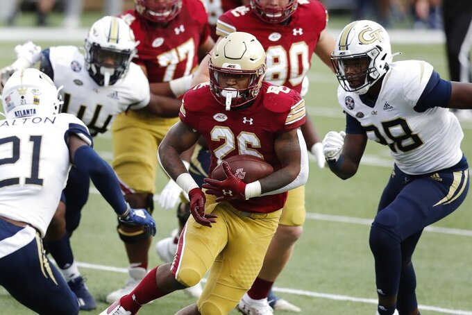 Boston College running back David Bailey (26) carries the ball against Georgia Tech defensive back Zamari Walton (21) and defensive lineman Curtis Ryans, right, during the first half of an NCAA college football game Saturday, Oct. 24, 2020, in Boston. (AP Photo/Michael Dwyer)
