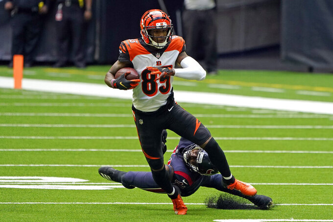 Cincinnati Bengals wide receiver Tee Higgins (85) catches a pass as Houston Texans inside linebacker Zach Cunningham reaches to tackle him during the first half of an NFL football game Sunday, Dec. 27, 2020, in Houston. (AP Photo/Eric Christian Smith)