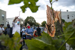 New York Mayor City Bill de Blasio talks to Christina Mitselos while looking at damage to her home from a trees knocked down by Isaias, Tuesday, Aug. 4, 2020, in the Queens borough of New York. (AP Photo/Frank Franklin II)