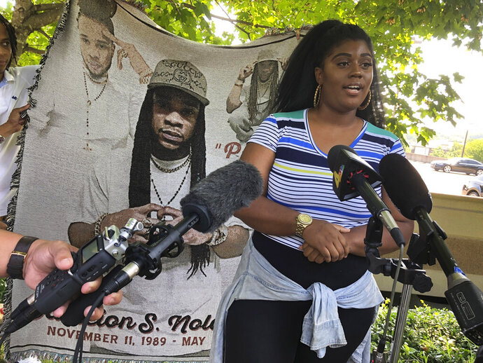 Kayla Cherry speaks at a news conference outside the headquarters of private prison company CoreCivic, Wednesday, July 10, 2019, in Nashville, Tenn. Cherry's nephew Dameion Nolan, pictured in a blanket behind her, died in May while he was an inmate at CoreCivic-run Whiteville Correctional Facility.  (AP Photo/Jonathan Mattise)