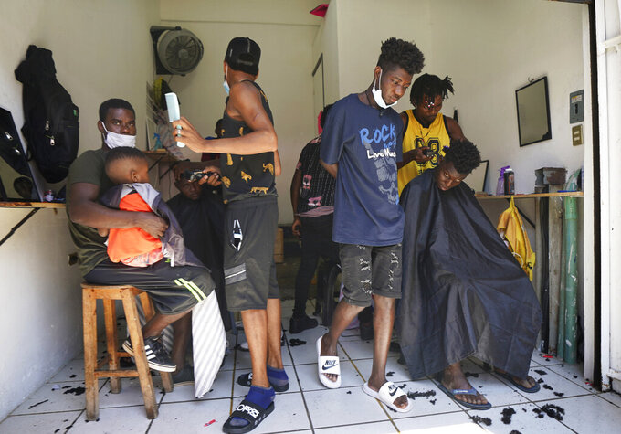 FILE - In this Sept. 3, 2021 file photo, Haitian migrants gather in a makeshift barbershop in Tapachula, Mexico. Thousands of mostly Haitian migrants have been stuck in the southern city of Tapachula, many waiting here for months and some up to a year for asylum requests to be processed. (AP Photo/Marco Ugarte, File)