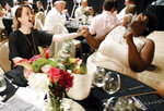 In this Aug. 4, 2019 photo, Amanda Felan talks to Jada Durden, right, during the Second Act Supper Club recent dinner at the Shreveport Municipal Auditorium in Shreveport, La. Anthony Felan learned an invaluable lesson after graduating from Le Cordon Bleu culinary institute and working on the ground-level of San Francisco's dining scene: If you're not invited to the exclusive, secret dinner parties, throw your own.  (Henrietta Wildsmith/The Shreveport Times via AP)