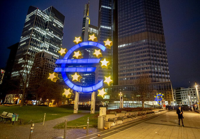 """FILE - In this Thursday, March 11, 2021 file photo, a man walks past the Euro sculpture in Frankfurt, Germany.  Facing unease over the spread of a more-contagious variant of the coronavirus, the European Central Bank (ECB) said Thursday July 22, 2021, it would maintain its stimulus in the form of ultra-low interest rates until inflation """"durably"""" reaches its 2% target. (AP Photo/Michael Probst, File)"""