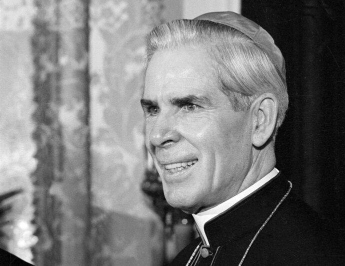 FILE - This Oct. 26, 2019 file photo shows Bishop Fulton J. Sheen at his office at the Propagation of Faith in New York.   The Catholic diocese of Rochester, N.Y., confirms it made the request for further investigations that prompted the Vatican to take the rare step of delaying Archbishop Fulton Sheen's journey to sainthood.   Pope Francis said last month that Sheen's beatification had been approved and would take place on Dec. 21, 2019 in Peoria, where he was ordained in 1919. The Peoria diocese announced Tuesday, Dec. 3 that the Vatican had postponed the ceremony indefinitely.  (AP Photo/Eddie Adams)
