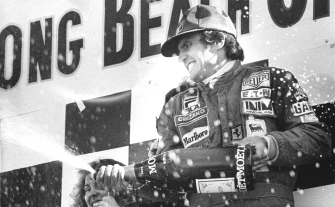 FILE - In this April 2, 1978 file photo, Argentina's Carlos Reutemann sprays champagne after winning the Long Beach Grand Prix in Long Beach, California. Reutemann, the Argentine ex-Formula One driver who entered politics after retirement, died at age 79 on Wednesday, July 7, 2021, according to his daughter Cora Reutemann. (AP Photo/File)