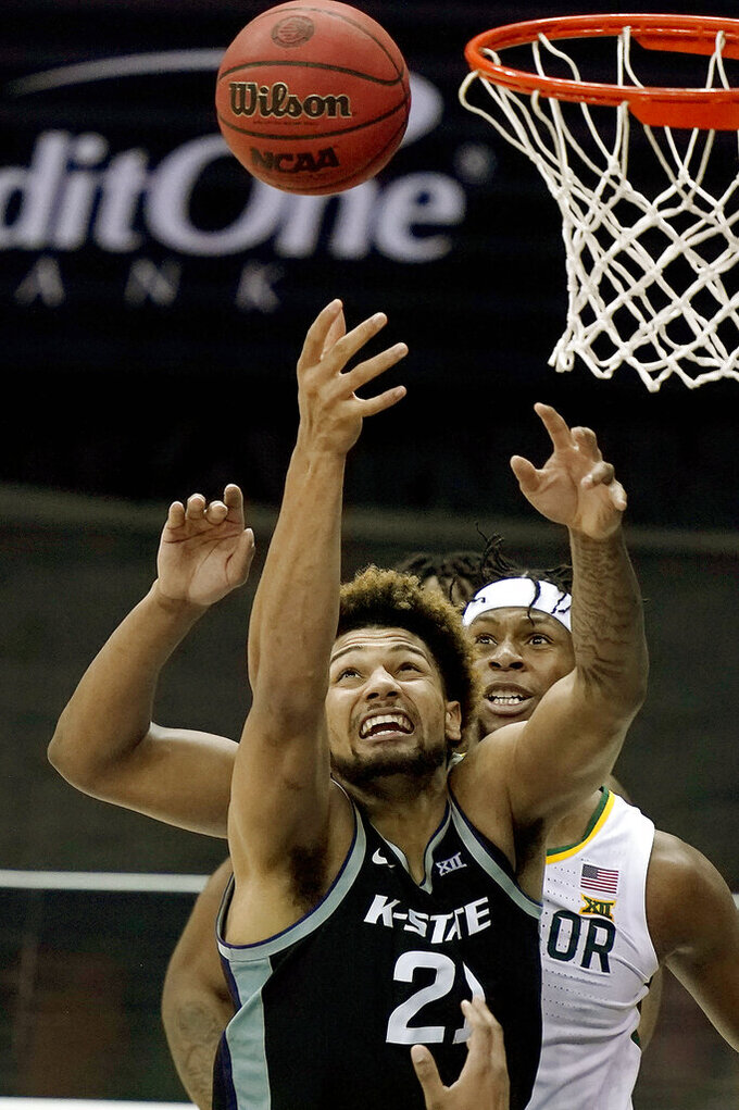 Baylor's Flo Thamba, back, and Kansas State's Davion Bradford (21) compete for a rebound during the second half of an NCAA college basketball game in the second round of the Big 12 men's tournament in Kansas City, Mo., Thursday, March 11, 2021. (AP Photo/Charlie Riedel)
