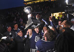 FILE -  In this Nov. 23, 2019, file photo, Yale's JP Shohfi, center, holds the Ivy League championship trophy during a celebration with teammates after their 50-43 doubl- overtime victory against Harvard in an NCAA college football game at the Yale Bowl in New Haven, Conn. At left is Yale University president Peter Salovey. The Ivy League was the first conference to scuttle its basketball postseason when the pandemic broke out during March Madness a year and a half ago. It was the first Division I conference to suspend fall sports in July 2020. Now the schools are getting back on the field the same way they left: cautiously. (Arnold Gold/New Haven Register via AP, File)
