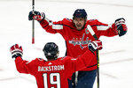 Washington Capitals left wing Alex Ovechkin (8) and center Nicklas Backstrom (19) celebrate after a goal during the second period of Game 1 of an NHL hockey Stanley Cup first-round playoff series against the Boston Bruins, Saturday, May 15, 2021, in Washington. It was later determined that the goal was scored by Capitals defenseman Brenden Dillon. (AP Photo/Alex Brandon)